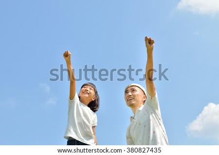 Parent and child raising hands towards the sky