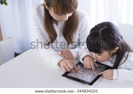 Parent and child to operate the tablet pc - stock photo