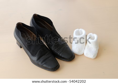 parent concept: baby booties next to mother's shoes - stock photo