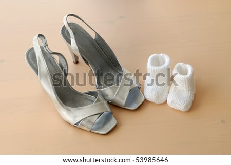 parent concept baby booties next to mother's shoes on wooden surface - stock photo