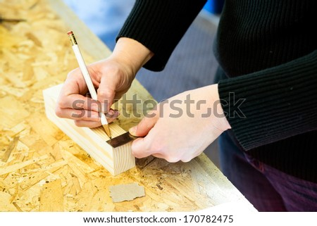 Parent draws stencil on wood block to be used as body for Pinewood Derby car - stock photo