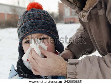 Parent helping a child to blow nose in winter outdoor.  - stock photo
