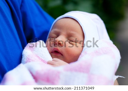 Parent holding his 3 days old newborn baby in blanket. Baby has neonatal jaundice. Focus on baby eyes. - stock photo