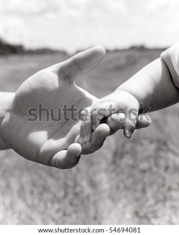 Parent holding little hand - stock photo