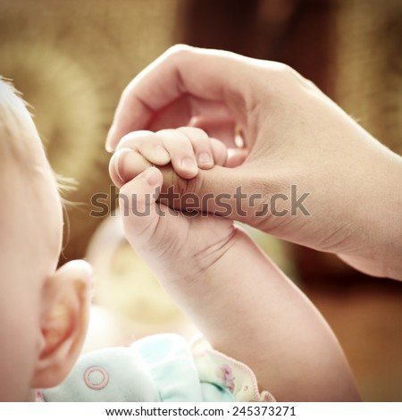 Parent holds Baby Hand Closeup - stock photo