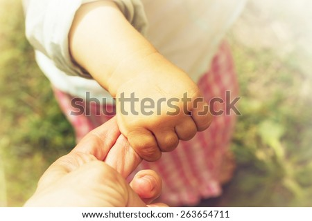 Parent holds the hand of a small child. Toned - stock photo