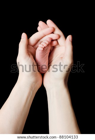 parent's hands cradling a newborn baby's foot