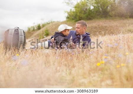 parent talking child nature lying grass  meadow field shallow DOF - stock photo