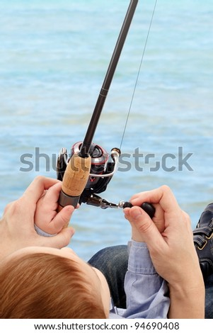 Parent teaching his child to fish on - stock photo