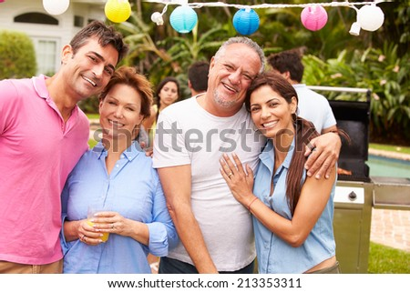 Parent With Adult Children Enjoying Party In Garden - stock photo