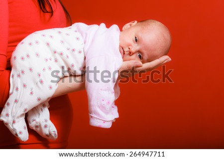 Parenting and love concept. one month old baby girl in the comfort of moms arms, red background - stock photo