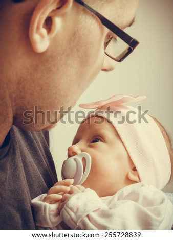 Parenting concept. Father holding delicate his newborn baby girl, at home - stock photo