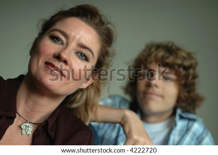 Parenting concept portrait of an attractive middle aged mother and her teenage son