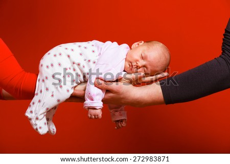 Parenting family and love concept. one month old baby girl sleeping in the comfort of parents arms, red background