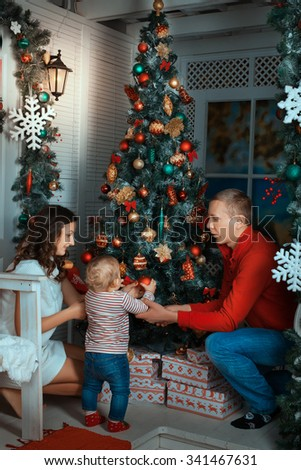 Parents and child near a Christmas tree. Parents helping daughter decorating a Christmas tree - stock photo