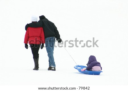 parents and child sledging - stock photo