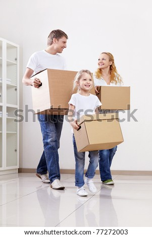Parents and child with cardboard boxes - stock photo