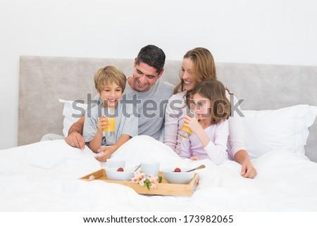 Parents and children having breakfast in bed - stock photo