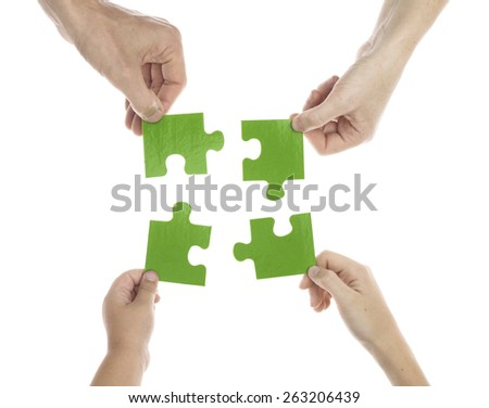 Parents and children holding jigsaw - stock photo
