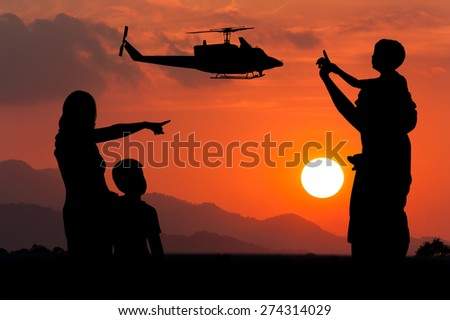 Parents and children look at the helicopter on the sky at sunset