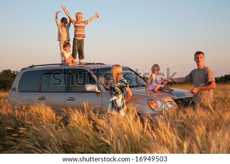 Parents and children on offroad car on wheaten field - stock photo