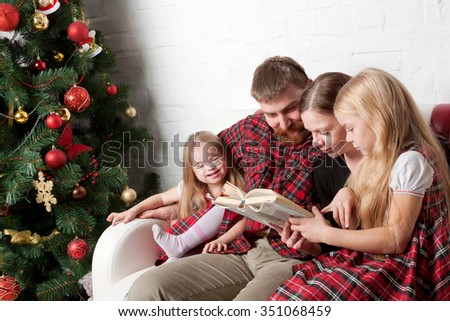 Parents and children reading stories together. Family sitting on the couch beside Christmas tree. - stock photo