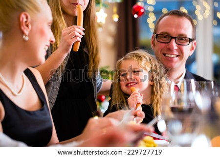 parents and children toasting with wine and water at Christmas eve dinner  - stock photo