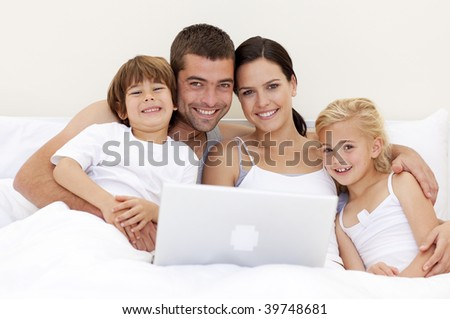 Parents and children using a laptop in bed