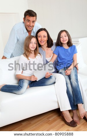 Parents and children using electronic tablet at home - stock photo