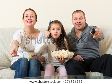 Parents and cute girl watching TV show together indoors. Focus on girl - stock photo