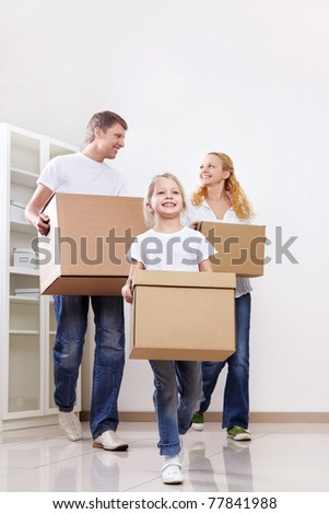 Parents and daughter are cardboard boxes indoors - stock photo