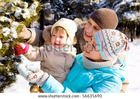 Parents and daughter decorating Christmas tree in a winter park