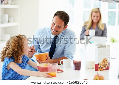 Parents And Daughter Having Breakfast In Kitchen Together - stock photo