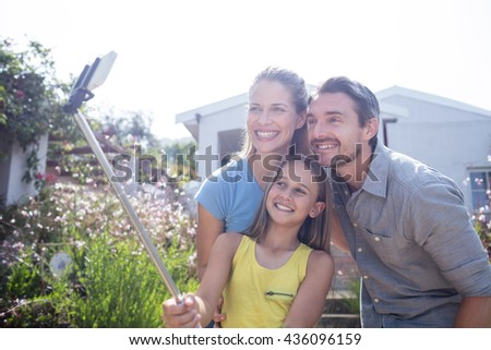 Parents and daughter in garden taking a selfie with selfie stick - stock photo