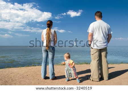 Parents and daughter on a beach - stock photo