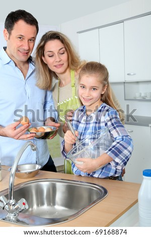 Parents and daughter preparing meal in home kitchen - stock photo