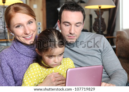 Parents and daughter sat with laptop on sofa - stock photo