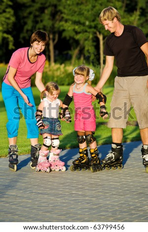 Parents and daughters  in roller skates - stock photo