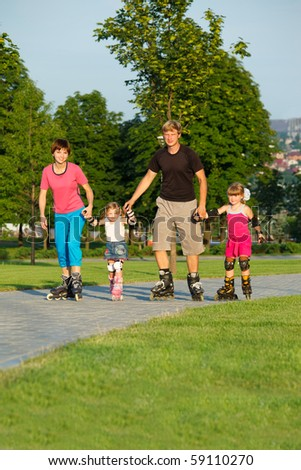 Parents and daughters roller skating - stock photo