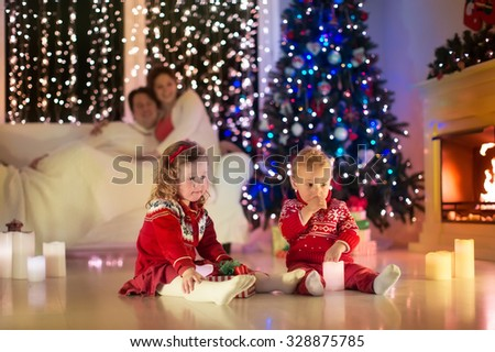 Parents and kids relax at fireplace on Christmas eve. Family with children celebrating Xmas. Decorated living room with tree, fire place and candles. Winter evening at home. Boy and girl open presents - stock photo