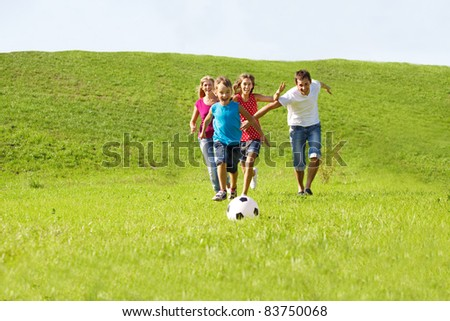 Parents and kids running to the ball - stock photo