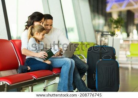parents and little daughter using laptop at airport - stock photo