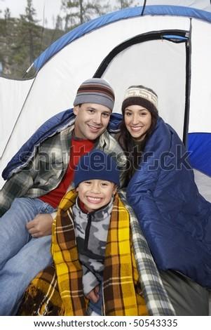 Parents and son (7-9) by tent, (portrait) - stock photo