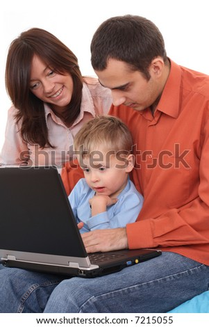 parents and son having fun with computer game on the sofa