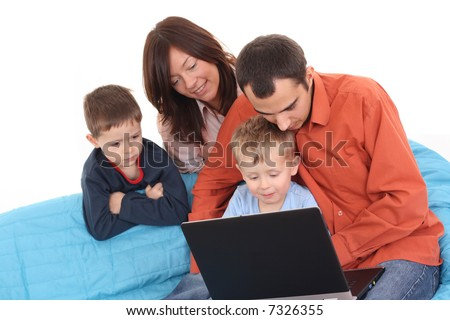 parents and son having fun with computer game on the sofa - stock photo