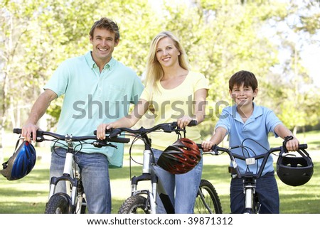 Parents And Son On Cycle Ride In Park - stock photo