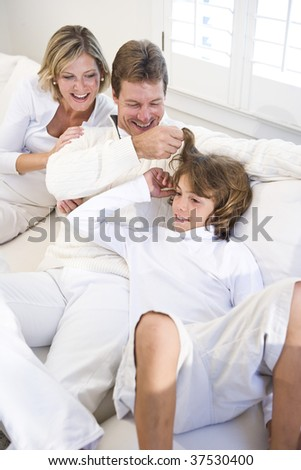 Parents and son relaxing on white sofa
