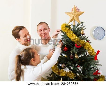 Parents and their child preparing for Christmas in the living room  - stock photo