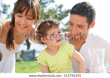parents and their little girl having picnic in the park - stock photo