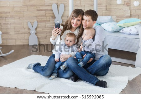 parents and  twins taking selfie by smartphone